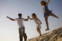 A family at the beach jumping off a sand dune Stock Photos