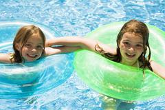 Two girls in a pool with inner tubes Stock Photos