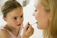 A daughter putting lip gloss on her mother Stock Photos