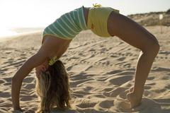 A woman doing yoga at the beach - stock photo