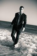 A man at the beach in formal attire - stock photo