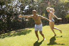 A couple playing in a sprinkler Kuvituskuvat