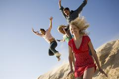 Two couples at the beach jumping off a sand dune - stock photo