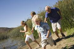 Grandparents and grandchildren by a lake - stock photo