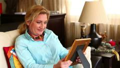Woman Looking at Photograph in Frame Stock Footage