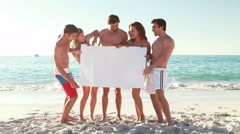 Friends holding blank poster at the beach Arkistovideo