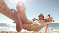Man relaxing in hammock on the beach Stock Footage