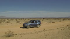 AERIAL: Blue SUV Driving Through Desert Dirt Road Stock Footage