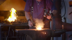 Slow motion spark shower as blacksmith hits hot metal on anvil 4K Stock Footage