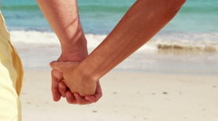 Couple on the beach looking out to sea holding hands Stock Footage