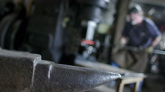 Rack focus from anvil to blacksmith at work 4K Stock Footage
