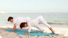 Peaceful couple stretching at the beach Stock Footage