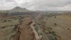 Dry african river bed aerial flyover shot with train tracks in dry season - stock footage