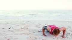 Fit man doing push ups on the beach Stock Footage