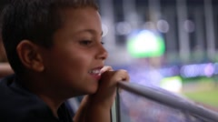 Kid watching a game from the stands at a stadium Stock Footage