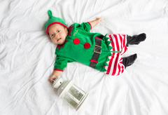 Baby in elf costume for christmas holiday on white background with a lantern Stock Photos