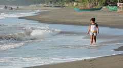 Filipino woman walking on the beach during a storm in Philippines Stock Footage