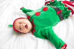 Baby in elf costume for christmas holiday on white background Stock Photos