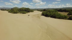 Aerial flyover a dry african river bed, dry season, people walking, car driving - stock footage