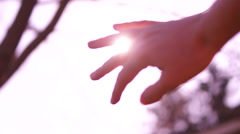 Sun's rays through fingers of female hand. - stock footage