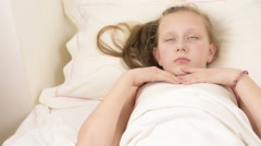 Beautiful big blue eyed teenage girl fall asleep on white bed, close up Stock Footage
