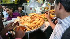 Indian men buying food and eating in front of a street food stand. Stock Footage