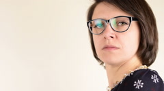 Angry beautiful green eyed serious brunette woman with black glasses portrait Stock Footage