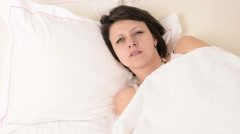 Beautiful big green eyed brunette woman fall asleep on white bed, portrait Stock Footage