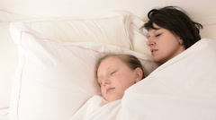Beautiful brunette mom and blonde blue eyed daughter fall asleep on bed Stock Footage