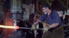 Side view of blacksmith working on hot metal bar in slow motion 4K Stock Footage