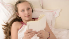 Beautiful big blue eyed teenage girl read book on white bed, close up Stock Footage