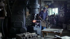 Wide view of blacksmith in workshop using industrial hammer 4K Stock Footage