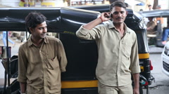 Indian men standing in front of a rickshaw on the street of Mumbai. Stock Footage