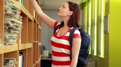 Pretty student taking book from shelf Stock Footage
