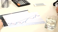 One businessman showing different graphics and something encircles pen for Stock Footage