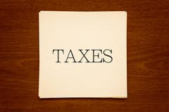 "Paper cards with word "" TAXES "" on wood background in sepia - stock photo"
