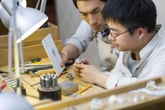 Male jewelers making a sapphire ring Stock Photos