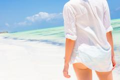 Woman on the beach in white shirt. Stock Photos