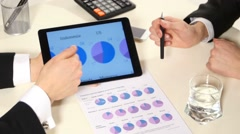 Business meeting: discussion of graphs the tablet, on such an important document Stock Footage