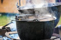Soup cooking in medieval pot Stock Photos
