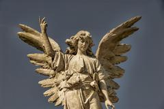A stone angel with wings spread against the sky. Kuvituskuvat