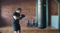 A young man boxing heavy bag during his workout in gym Stock Footage