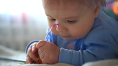 Little boy with nipple plays with toy Stock Footage