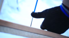 Screw being screwed into a piece of deck board with an electric screwdriver - stock footage