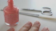 Woman applying coral nail polish Stock Footage