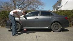 Man jacks up car outdoors Stock Footage