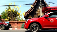 CHIANG MAI - March 2015: Traffic and tourists in front of ancient wooden temple. Stock Footage