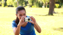 Stock Video Footage of Smiling brunette taking pictures in the park