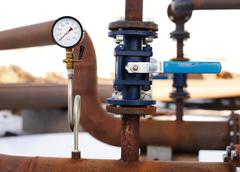 blue valve and manometer on rusty pipe - stock photo