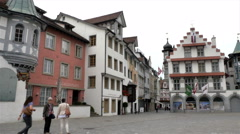Locals stroll the plaza at the Abbey of Saint Gall in St. Gallen, Switzerland - stock footage